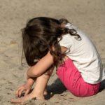 Small sad girl on the beach